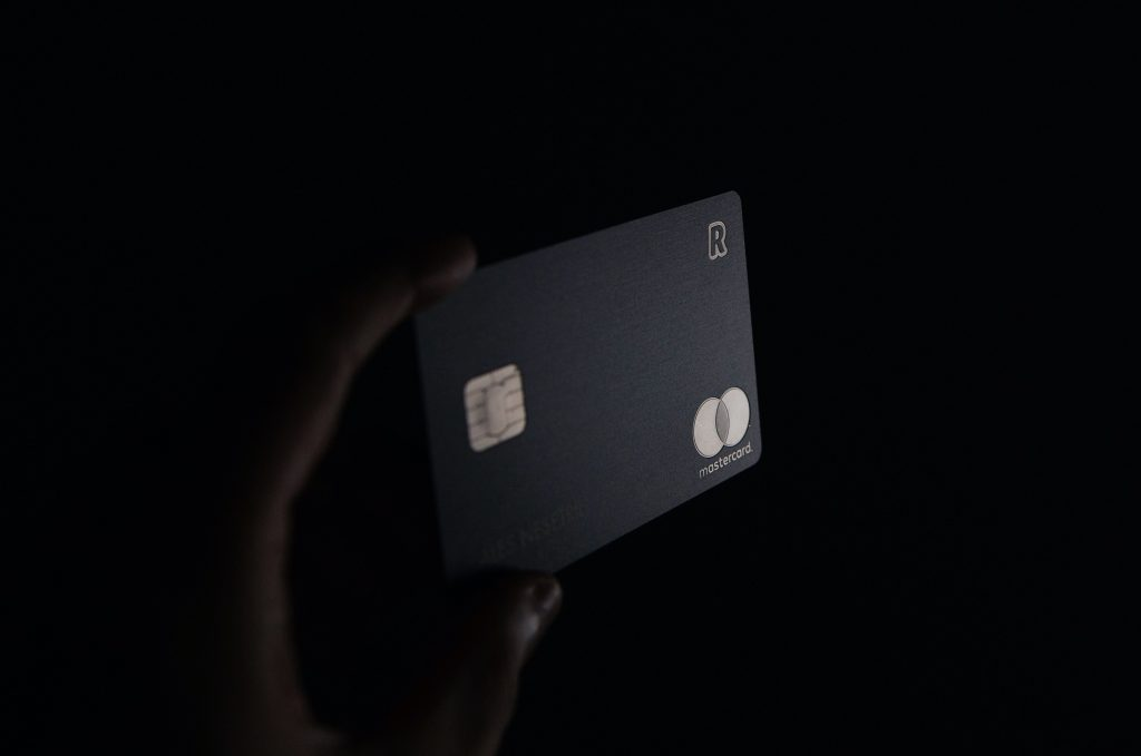 Person holding a credit card in the air