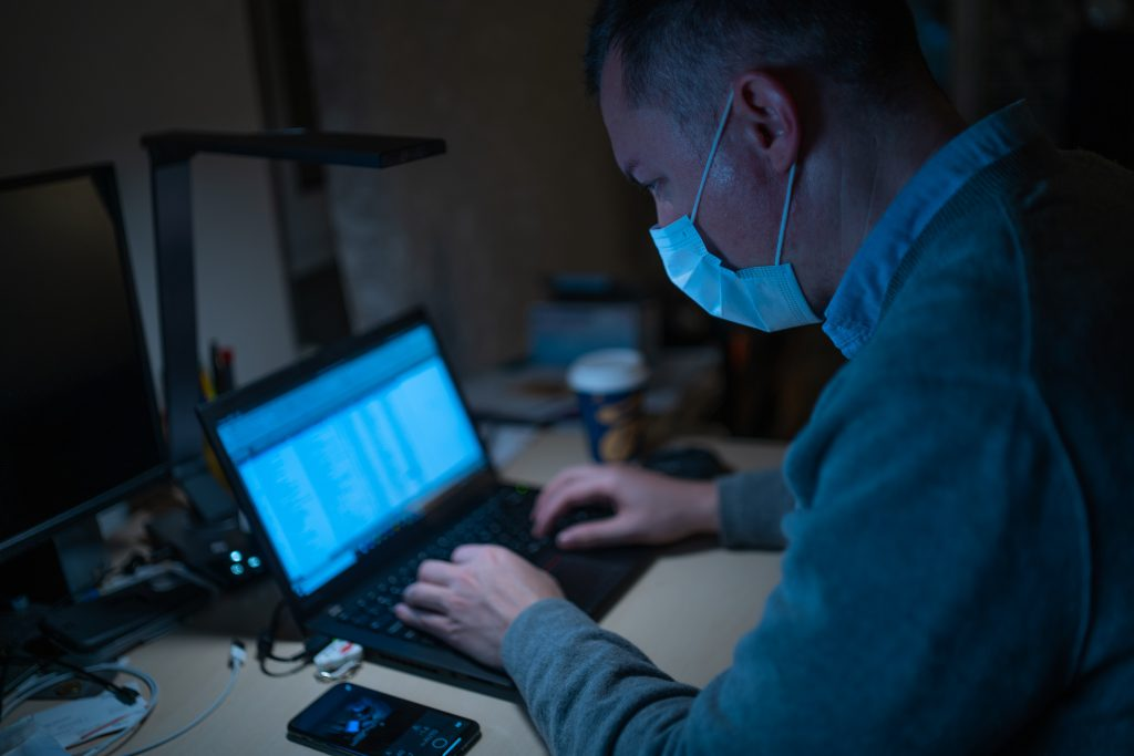 Man With Face Mask Types on Computer